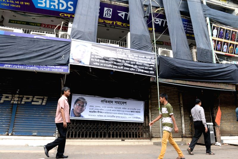 People pass by a banner bearing the image of Bangladeshi publisher Faisal Arefin Dipan, who was murdered in an attack by suspected Islamists in Dhaka, Bangladesh, Nov. ...