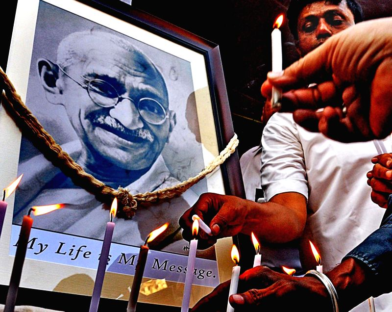 People pay tribute to the portrait of Mahatma Gandhi on his death anniversary in Mumbai on Jan 30, 2018.
