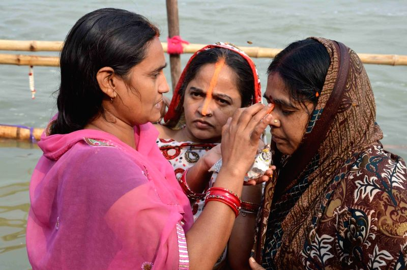 People perform Chhath Puja rituals on the banks of the Ganga river in Patna, on Nov 16, 2015.