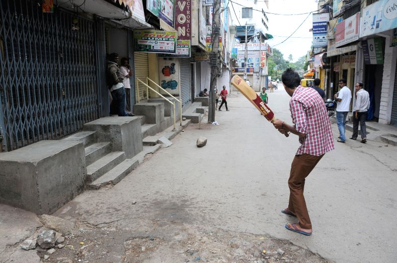 People play cricket on the streets of Bangalore as Kannada outfits call for a 12-hour strike to protest against crime against women on July 31, 2014.
