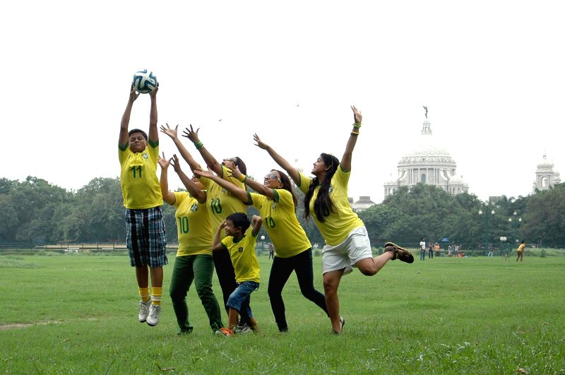 People play football wearing jersey of Brazilian football team at Maidan in Kolkata on June 22, 2014.
