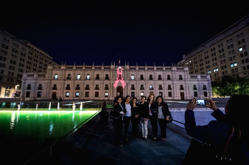 People pose in front of the image of a red ribbon projected on the Palace of La Moneda in commemoration of the World AIDS Day, in Santiago, capital of Chile, on ...