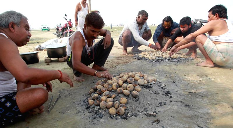 People prepare Bati (roti) after taking holy dip in the Sangam - the confuelce of three rivers, the Ganga, the Yamuna and Saraswati - in Allahabad on Nov 29, 2015.