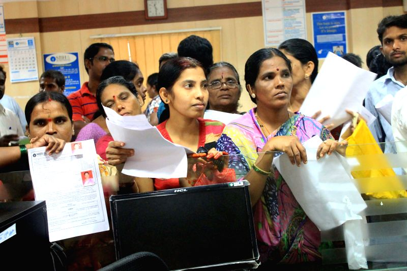 People queue up at a bank to open bank accounts under Pradhan Mantri Jan Dhan Yojana in Hyderabad on Aug 28, 2014.