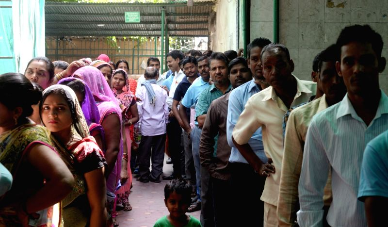 People queue-up at a polling booth to cast their votes during MCD polls in New Delhi on April 23, 2017. The main contest in Delhi is between the three major players in the city's politics ...