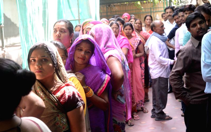 People queue-up at a polling booth to cast their votes during MCD polls in New Delhi on April 23, 2017.  Over 2,500 candidates are in the fray for elections to North Delhi Municipal ...