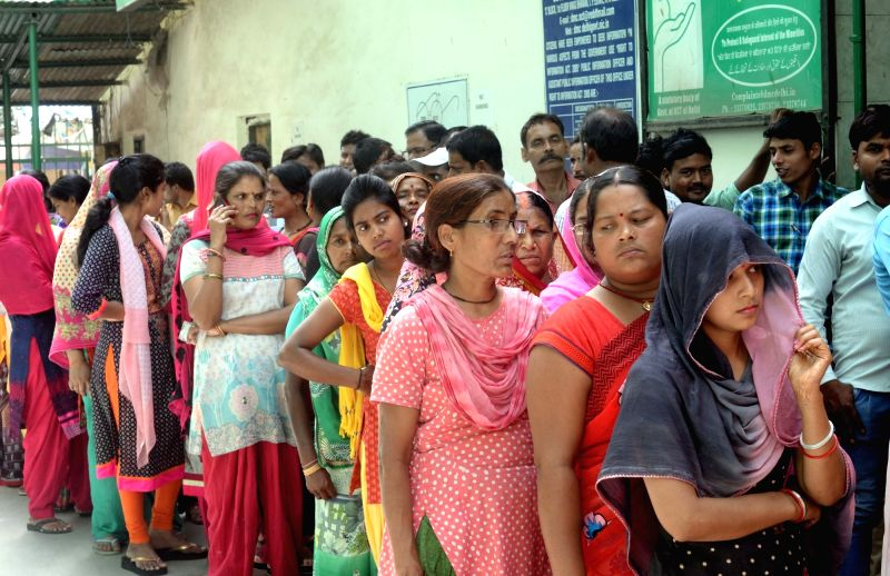 People queue-up at a polling booth to cast their votes during MCD polls in New Delhi on April 23, 2017. Over 1.32 crore eligible voters are likely to exercise their franchise at 13,022 ...