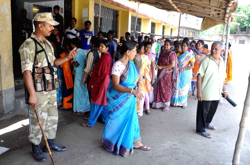 People queue-up to cast their votes at a polling booth during the ninth phase of 2014 Lok Sabha Polls in Kolkata on May 12, 2014.