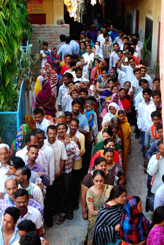 People queue-up to cast their votes at a polling booth during the ninth phase of 2014 Lok Sabha Polls in Varanasi on May 12, 2014.