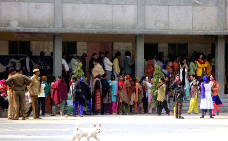 People queue-up to cast their votes at a polling booth during Delhi Assembly Polls at Dakshinpuri, in New Delhi, on Feb 7, 2015.