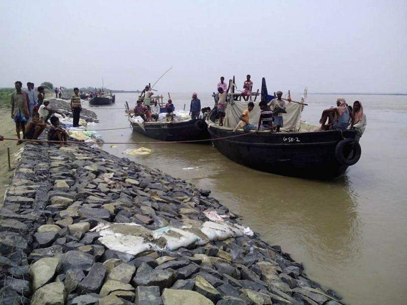 People reinforce an embankment so as to check soil from being swept away by the river in Malda district of West Bengal on Aug 24, 2014.