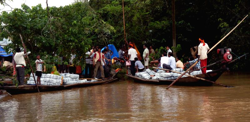 People representing Indian Red Cross Society arrive at Pandiakera village in Puri district of Odisha, with relief materials on Aug 10, 2014. The flood affected village was out of bounds for last five