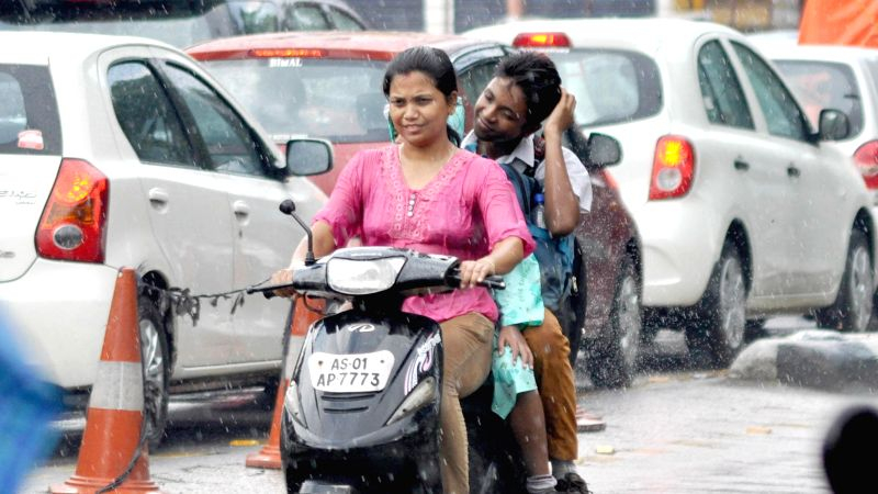 People ride bike as it suddenly rains during a hot summer day in Guwahati on June 17, 2014.