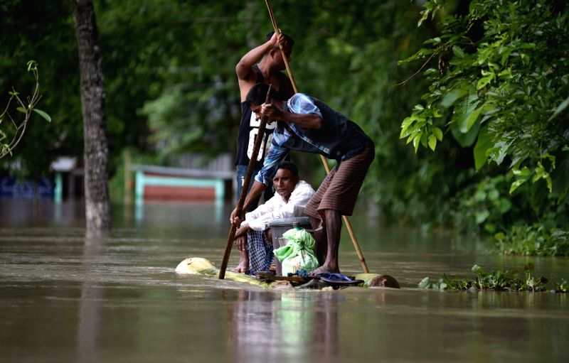People row a raft in flood hit Numaligarh area of Assam's Golaghat, on Aug 2, 2018.