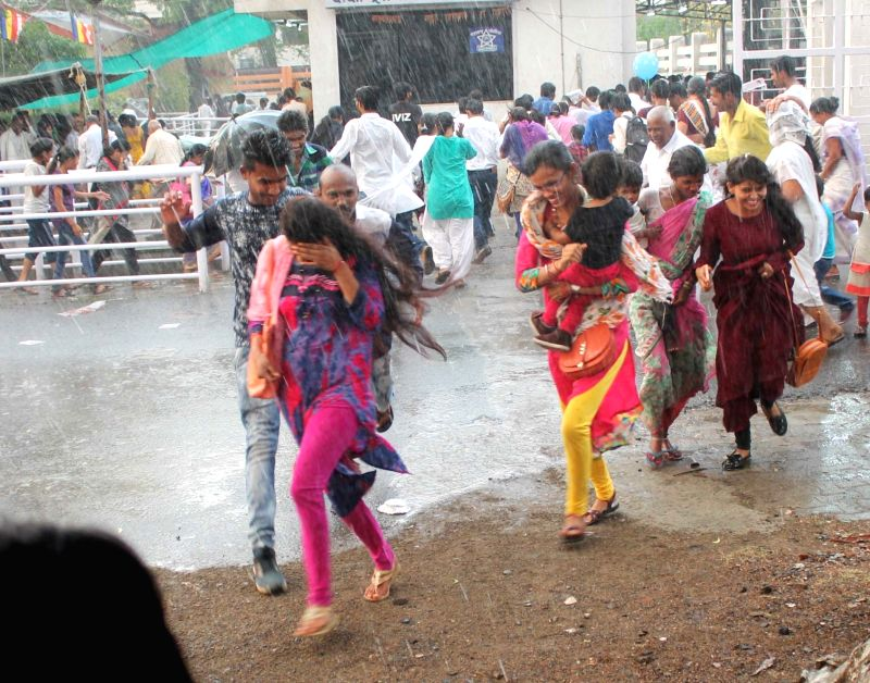 People run for cover during rains, in Nagpur on April 14, 2018.