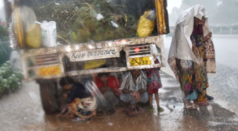 People shield themselves with a plastic; under the truck as rains lashed the city , in New Delhi, on Aug 10, 2018.