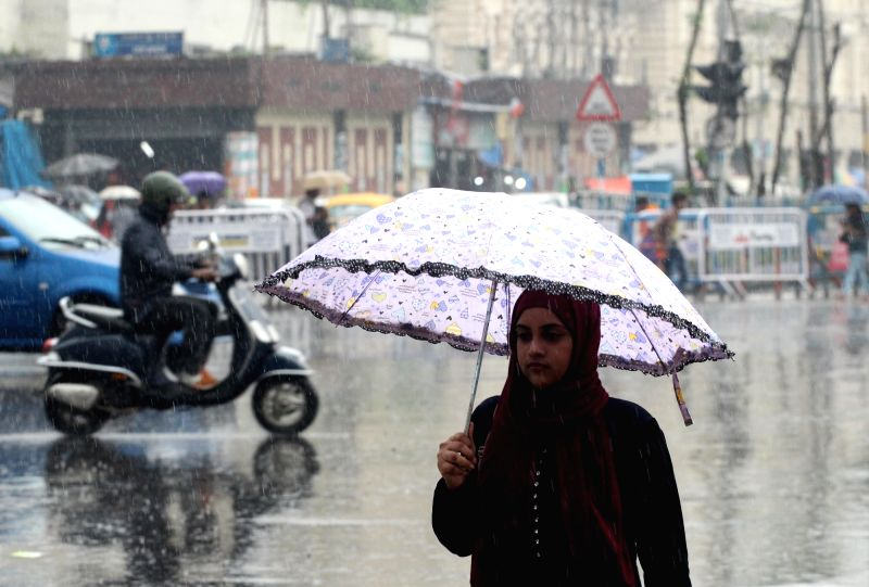 People shield themselves with umbrellas as rains lash Kolkata on July 31, 2018.