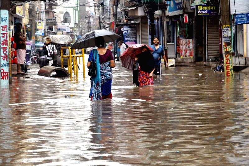 People shield themselves with umbrellas as they struggle through a water-logged street, in Patna on July 26, 2018.