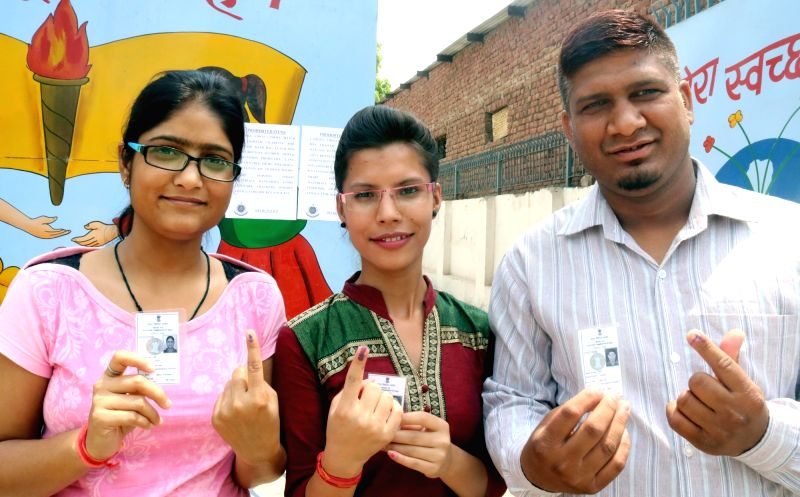 People show their show their forefingers marked with phosphorous ink after casting vote at a polling booth during Municipal Corporation of Delhi (MCD) Polls in New Delhi, on May 15, 2016.
