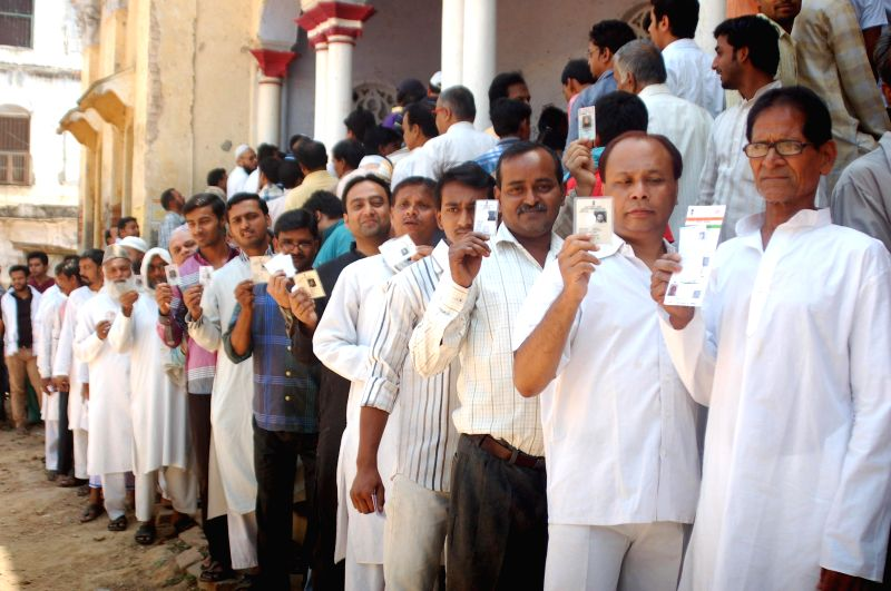 People  show their voter's identity card as they queue-up to cast their votes at a polling booth during the ninth phase of 2014 Lok Sabha Polls in Varanasi on May 12, 2014.
