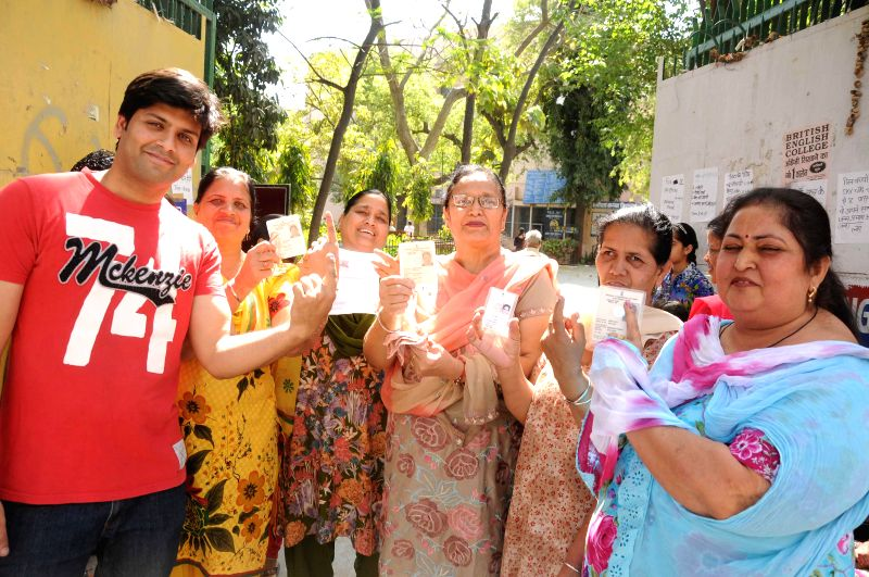 People show their voter's identity cards at a polling booth during the third phase of 2014 Lok Sabha Polls in New Delhi on April 10, 2014. Elections are being held in 91 parliamentary constituencies .