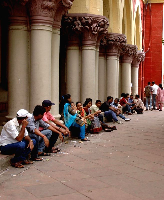People sit in Calcutta High Court premises as lawyers go on a strike in Kolkata on June 24, 2014.