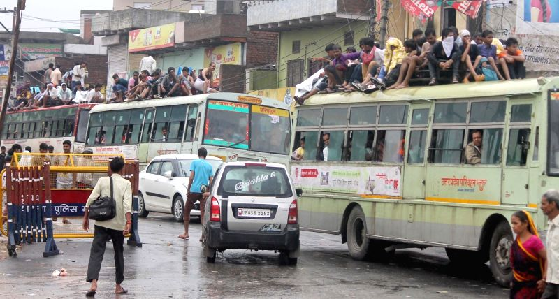 People sitting on the roof of an overland bus to participate at Govardhan Parikrama procession in Mathura on July 17, 2016.