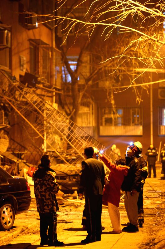 People stand in front of the building where an explosion happened in the Yongle community of Shijingshan District in Beijing, capital of China, on Dec. 7, 2015. No ...