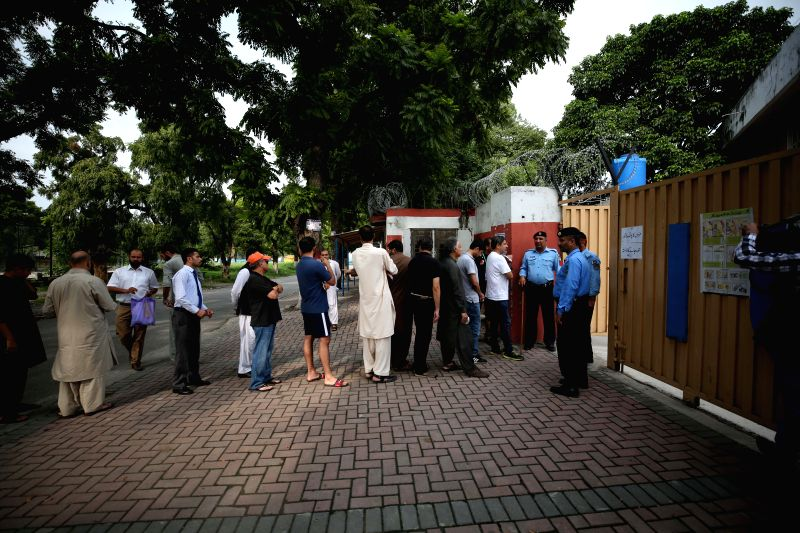 :People stand in queue to cast their votes outside a polling station in Islamabad, capital of Pakistan, on July 25, 2018. Pakistanis started casting votes in ...