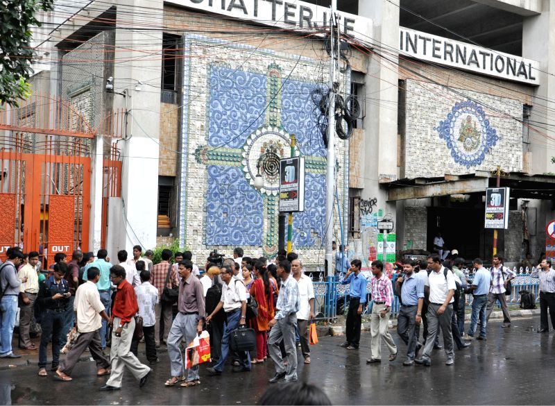 People stand outside Chatterjee International building that houses a large number of offices of multinationals and public sector units in Kolkata on Sept 3, 2014. Four people fell ill  after a fire ..