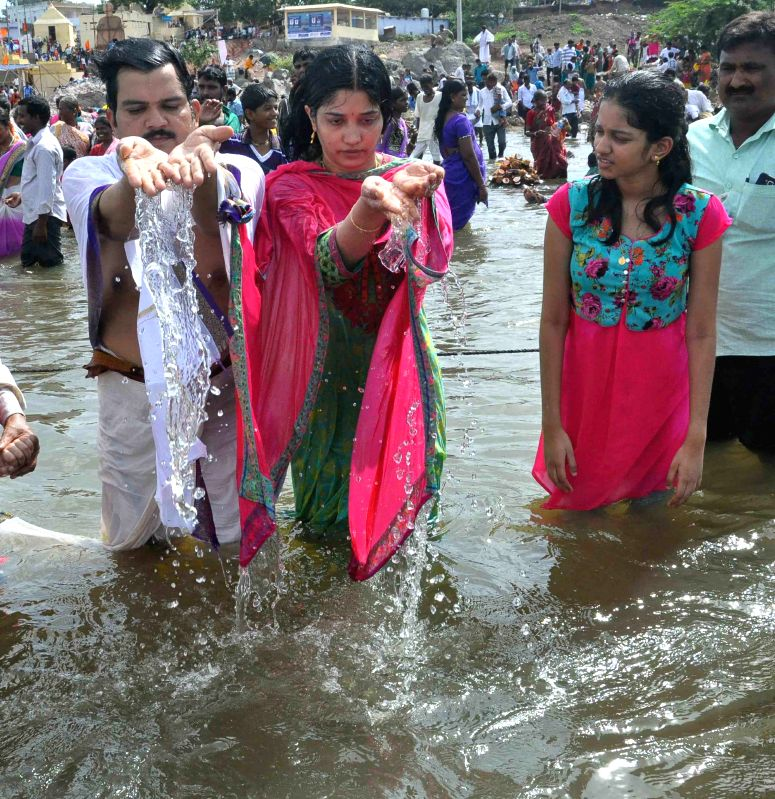 People take holy dip in the Godavari river during Godavari Maha Pushkarams in Karimnagar of Telangana, on July 24, 2015.