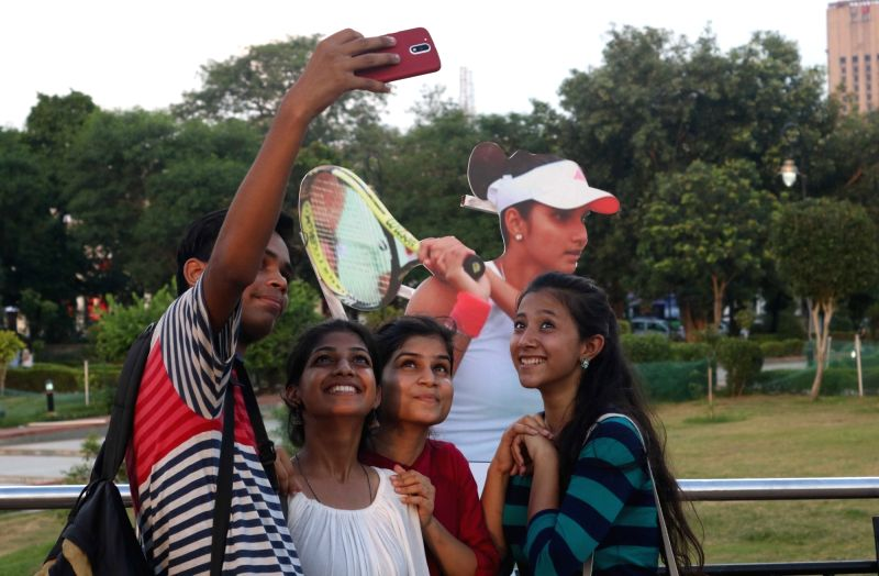 People take selfies with a cut-out of Sania Mirza at an exhibition ahead of Rio 2016 Olympics at Central Park in New Delhi on Aug 5, 2016. - Sania Mirza