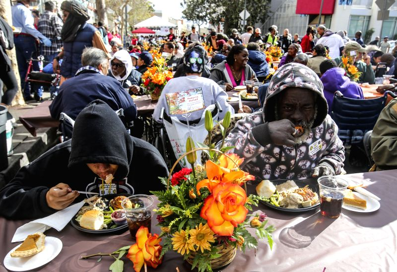 People take their Thanksgiving meal in Los Angeles, the United States, on  Nov. 25, 2015. Thousands of Skid Row residents and homeless people from downtown and ...