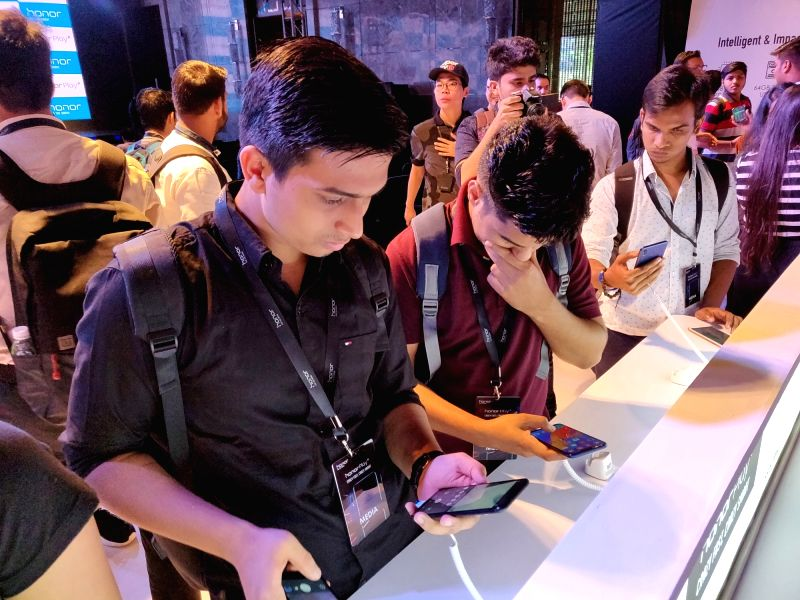 People try their hands at the newly launched Honor Play smartphone in New Delhi, on  Aug 6, 2018