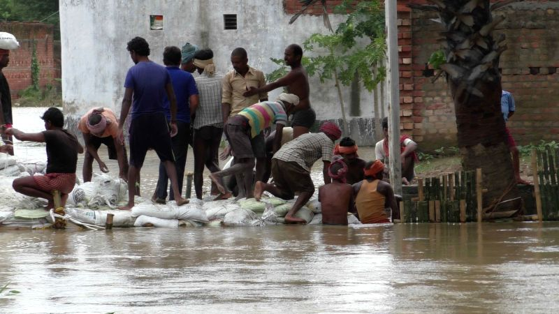 People try to prevent the flow of water with sacks of sand during floods in Bihar's Nalanda district on Aug 8, 2018.