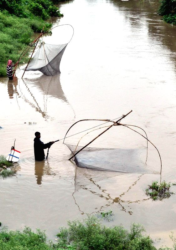 People use Chinese nets as they fish in a river of Agartala where water level has gone up after two days of incessant rains, on June 22, 2014.