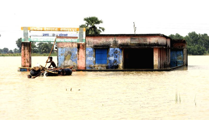 People use rafts as a means of transportation in flood affected Patna district of Bihar on Aug 19, 2014.