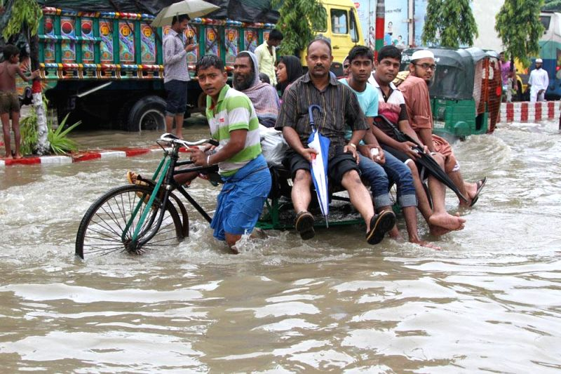 People use rickshaws to cross water logged streets of Chittagong's Muradpur in Bangladesh on June 20, 2014.