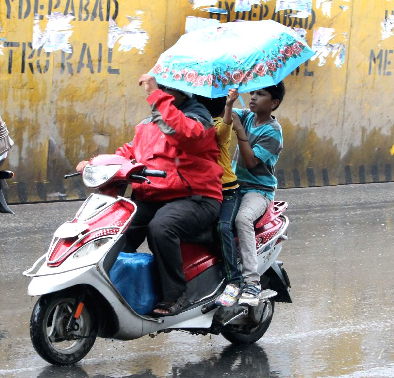 People use umbrella to shield themselves from heavy rains in Hyderabad on Aug 8, 2014.