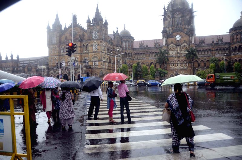 People use umbrellas to protect themselves from rains in Mumbai on July 22, 2015.