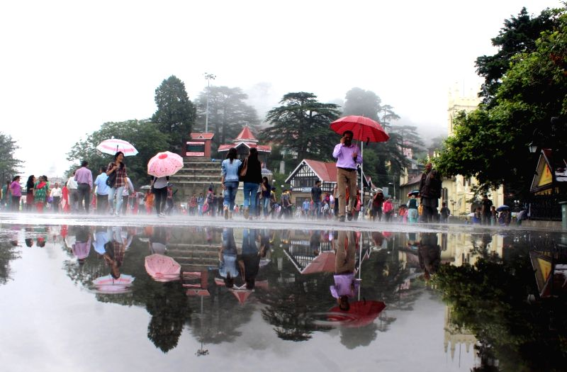 People use umbrellas to protect themselves from rains in Shimla on July 22, 2016.