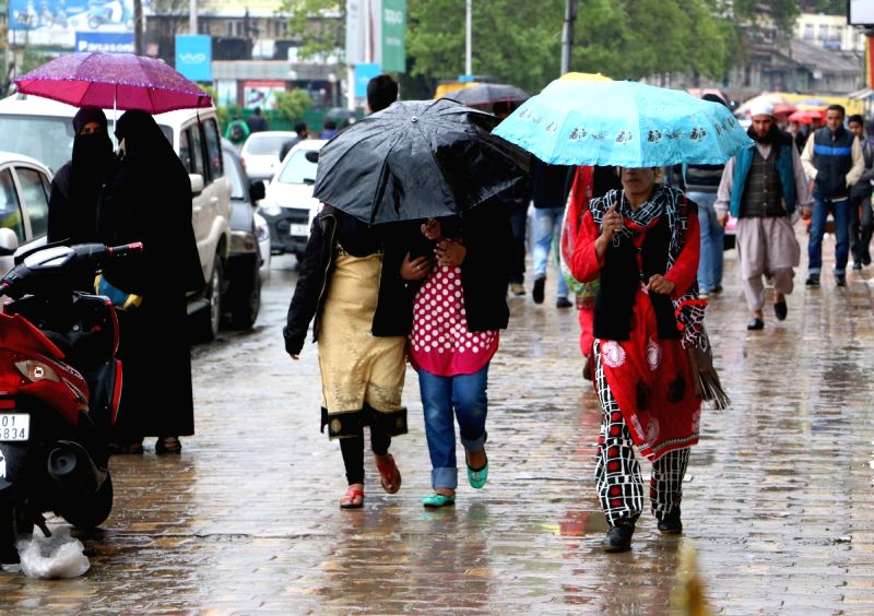 People use umbrellas to protect themselves from rains in Srinagar on April 29, 2017.