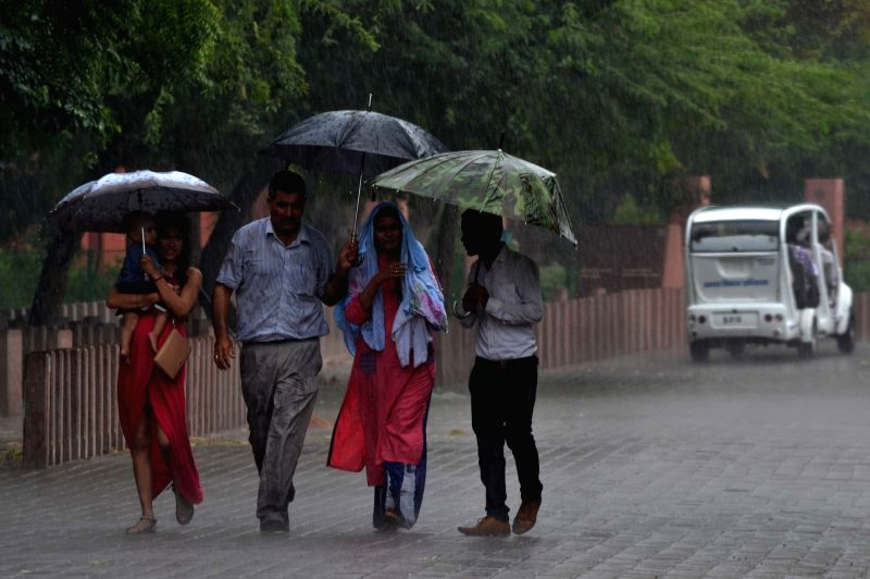 People use umbrellas to protect themselves from rains in Agra on June 8, 2017.