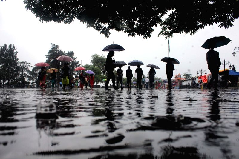 People use umbrellas to shield themselves during rains, in Shimla on July 17, 2018.