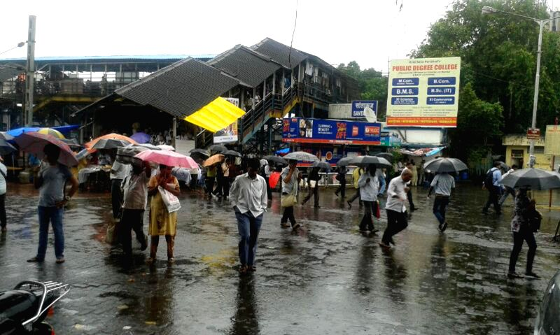 People use umbrellas to shield themselves from rains in Mumbai on July 2, 2014.