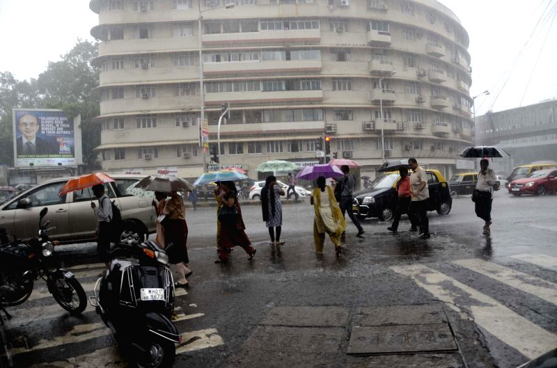 People use umbrellas to shield themselves from rains in Mumbai on July 7, 2014.