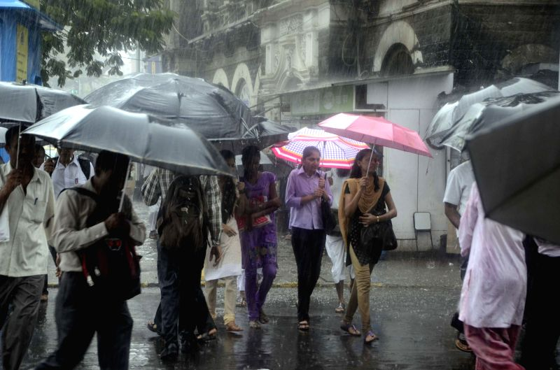 People use umbrellas to shield themselves from rains in Mumbai on July 15, 2014.