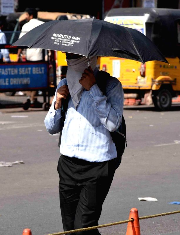 People use umbrellas to shield themselves from scorching sun in Hyderabad on March 25, 2017.