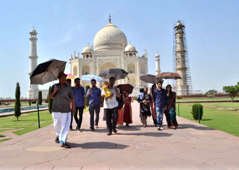 People visiting the Taj Mahal use umbrellas to shield themselves from direct sun in Agra on May 9, 2017.