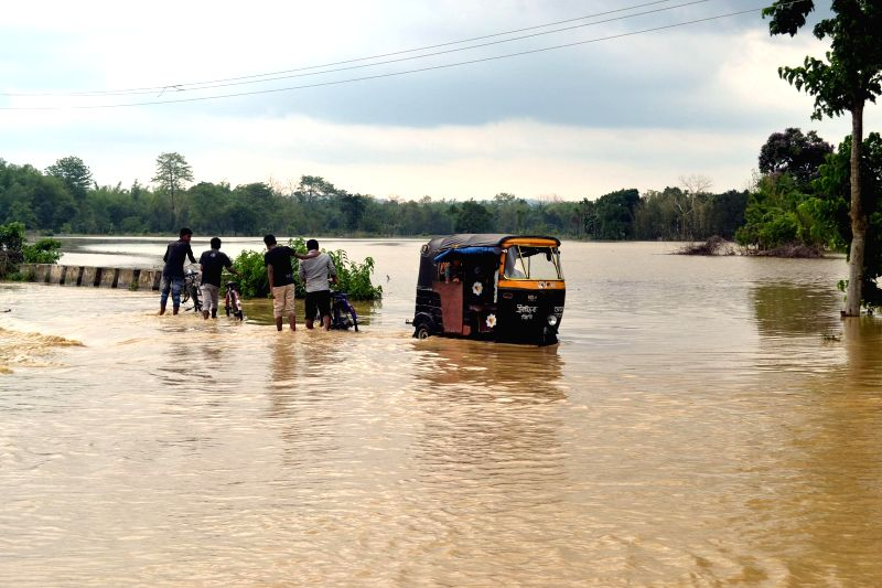 People wade through a water logged street after heavy rains hit Kamalpur of Dhalai district of Tripura on May 9, 2014. Several houses were destroyed and crop spoiled in the rains.